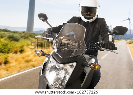 Biker in helmet and leather jacket riding on the road.
