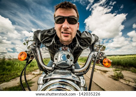 Biker in sunglasses and leather jacket racing on the road - stock photo