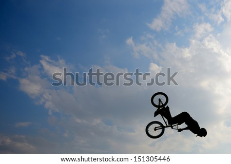 Biker is doing a trick in the air on his bmx bike