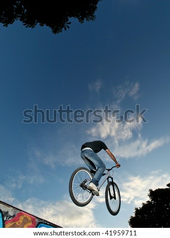 Biker jumping high on a ramp against blue sky - stock photo
