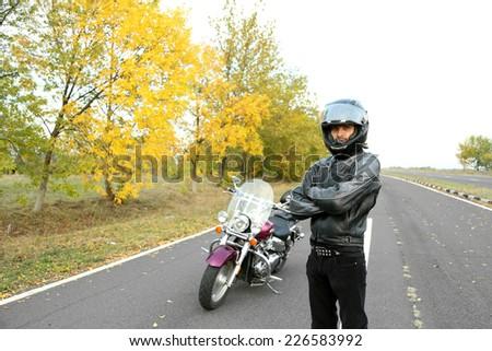 Biker man and his bike, outdoor - stock photo
