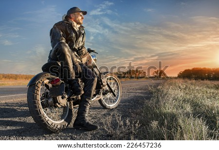 Biker man looking on sunrise - stock photo