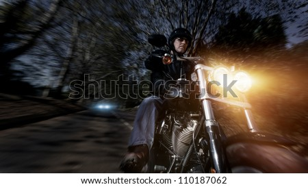 Biker man riding his motorbike fast with motion blur and lens flare at night while being chased by a car in the distance.