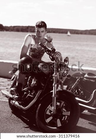 Biker man sits on a bike - stock photo
