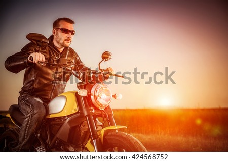Biker man wearing a leather jacket and sunglasses sitting on his motorcycle looking at the sunset, racing on the road. Filter applied in post-production. - stock photo