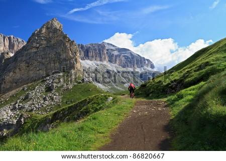 biker on high mountain road in Pordoi pass, Italian Dolomites - stock photo