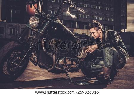 Biker repairing his custom motorcycle bobber on a road  - stock photo