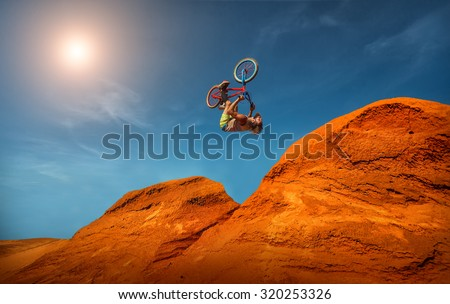 Biker rides on road in the high mountains of sand dunes . Background blue sky with clouds - stock photo