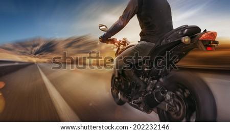 Biker riding motorcycle - stock photo