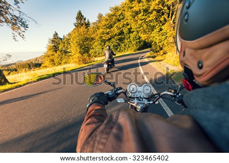 Biker riding motorcycle  on road in morning sunny day. Shot from behind - stock photo