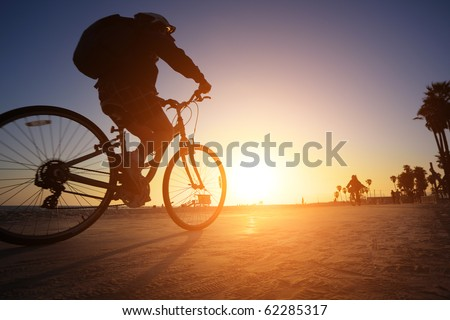 Biker silhouette riding along beach at sunset - stock photo