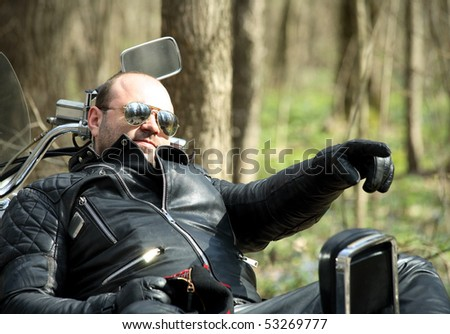 biker sitting on his motorcycle ,  relax, and shows hand sideways - stock photo