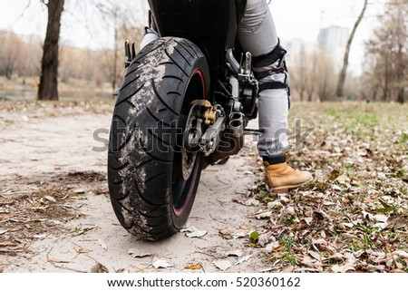Biker sitting on motorcycle on an empty road, close-up view on rear wheel. View from land. Transportation concept.