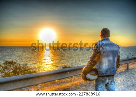 Biker with helmet looking at the sun at sunset. Heavy processed for hdr tone mapping effect - stock photo