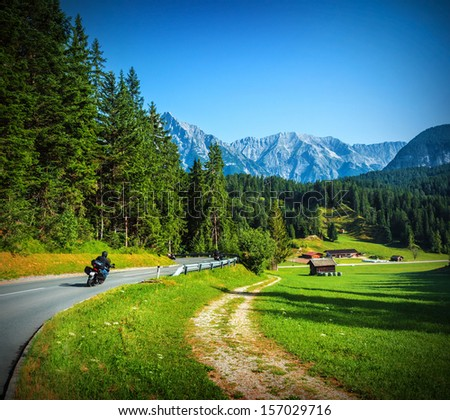 Bikers on mountainous road, touring across Alpine mountains, along little village, beautiful landscape, travel and tourism concept - stock photo