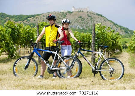 bikers, ruins of Devicky castle with vineyard, Czech Republic - stock photo