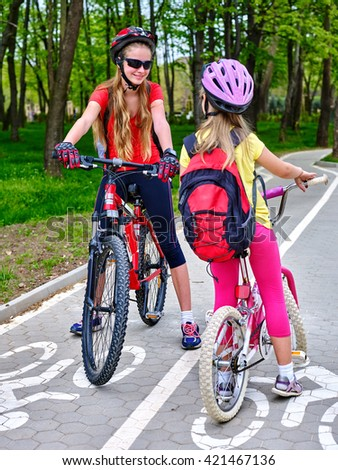 Bikes bicyclist girl. Two girls wearing bicycle helmet and glass with rucksack ciclyng bicycle. Girls children cycling meet on white bike lane. Bike share program save money and time at city street.  - stock photo