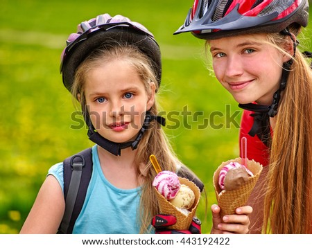 Bikes bicyclist girls. Girls wearing bicycle helmet with rucksack rides bicycle. Girls children are bicycling in summer park. Girls biking eating ice cream cone . Bicyclist is looking at each other. - stock photo