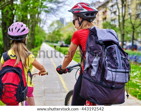 Bikes bicyclist girls wearing bicycle helmet with rucksack ciclyng bicycle. Girls children cycling on yellow bike lane. Bike share program save money and time at city street. Back view. - stock photo