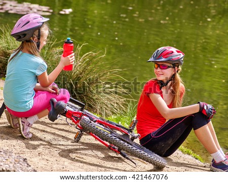 Bikes cycling family. Happy mother and daughter  rides bicycle. Family have  rest near water in park. Kid drinking bottle water. Bicycles are on coast.  - stock photo