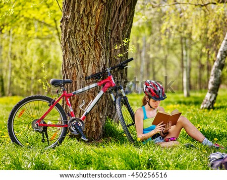 Bikes cycling girl. Girl rides bicycle. Girl in cycling read book on rest near bicycle. Cycling wearing helmet. Cyclist looking at book. - stock photo