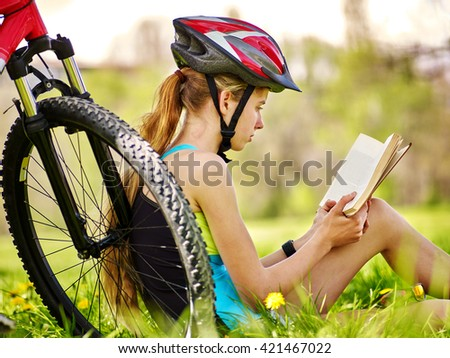 Bikes cycling girl. Girl rides bicycle. Girl in cycling read book on rest near bicycle. Cycling is good for health. Cyclist back view. - stock photo