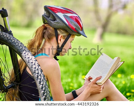 Bikes cycling girl. Girl rides bicycle. Girl in cycling read book on rest near bicycle. Cycling is good for health. Cyclist looking at camera. - stock photo