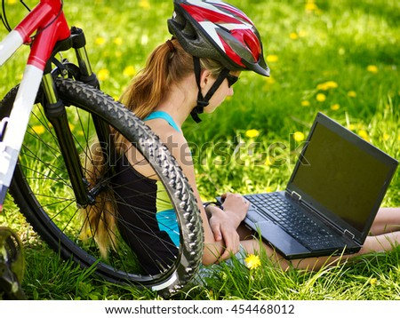 Bikes cycling girl. Girl rides bicycle. Girl in cycling sitting near bicycle and watch laptop. Cycling is good for health. Bicyclist wearing helmet. - stock photo