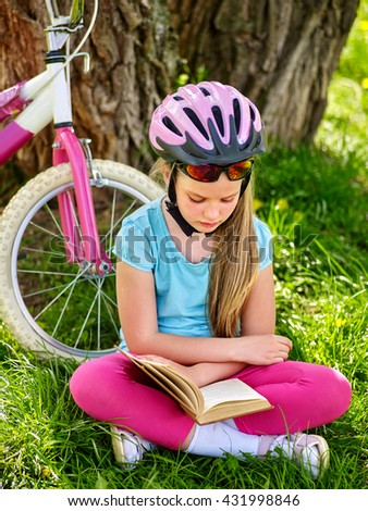Bikes cycling girl. Girl rides bicycle. Girl in cycling sitting on green grass near bicycle and read book on rest near bicycle. Cycling is good for health. - stock photo