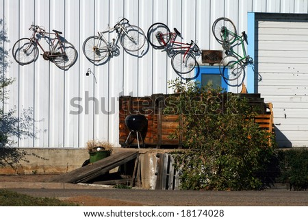 Bikes mounted on the outside of a warehouse wall. - stock photo