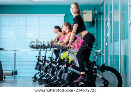 Biking. Athletic girl pedaling on the simulator until her four girlfriends athletes pedaling on a stationary bike at the gym. - stock photo