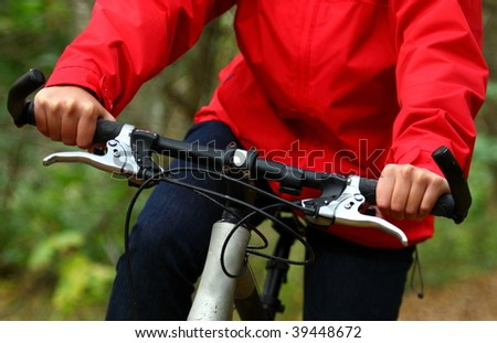 Biking in the forest.. Closeup of woman on mountainbike. - stock photo