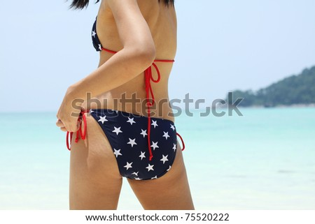 Bikini girl, A girl binding her bikini by the sea. - stock photo