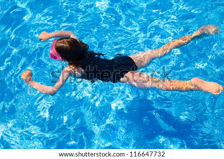bikini kid girl swimming on blue tiles pool in summer vacation - stock photo