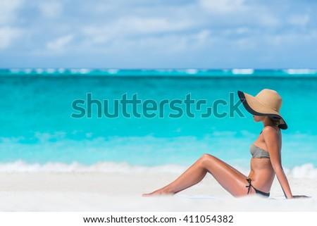 Bikini woman beach vacation sun tanning relaxing on beach. Suntan concept. Unrecognizable female adult enjoying the sunshine with straw hat sunbathing under the tropical sun on Caribbean vacation. - stock photo
