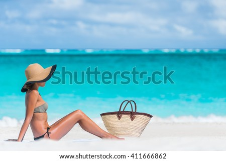 Bikini woman beach vacation sun tanning relaxing on beach. Suntan concept. Unrecognizable female adult enjoying the sunshine with straw hat sunbathing under the tropical sun on Caribbean vacation. - stock photo