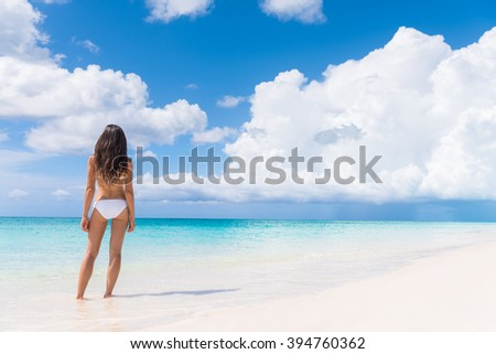 Bikini woman with slim sexy body standing from behind on tropical white sand beach in Caribbean looking over the perfect turquoise ocean. Luxury living vacation destination. - stock photo