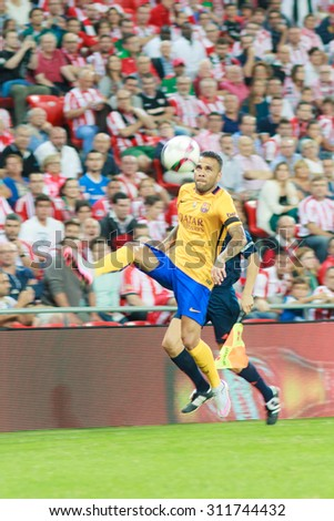 BILBAO, SPAIN - AUGUST 14: Daniel Alves jumps to control the ball in the match of the Spain Supercup Athletic Club Bilbao vs Barcelona on August 14, 2015 in Bilbao, Spain