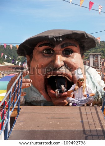 BILBAO, SPAIN - AUGUST 28: Kids enter the Gargantua during the Semana Grande Festival in Bilbao, this caricature figure is taken to the streets during festivities, on August 28, 2011 in Bilbao, Spain - stock photo