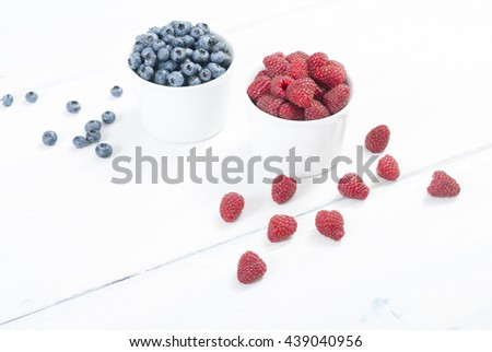 bilberry and raspberry fruits at white ceramic cup, on bright wood table