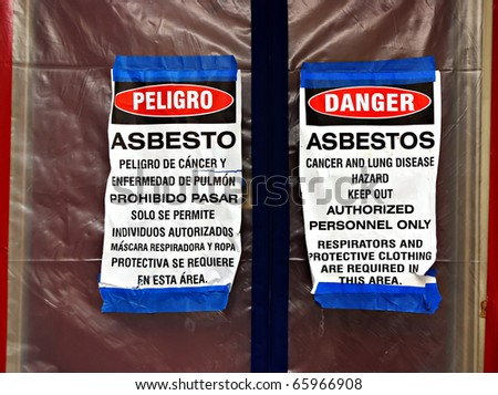 Bilingual asbestos warning signs on plastic covering a front door - stock photo