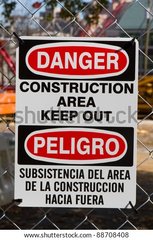 Bilingual sign in both the english and spanish language for minorities warns to keep out because of danger in a construction area is attached to fence.