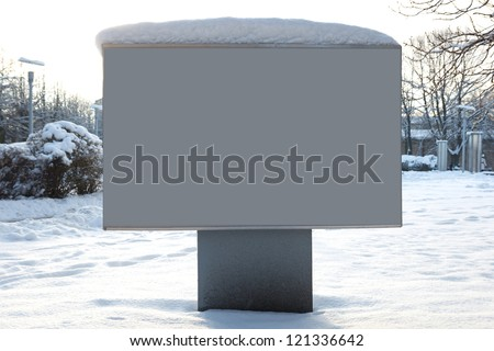 Billboard covered with snow on the background of the park. - stock photo