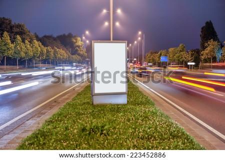 Billboard in the city street by night, blank screen - stock photo