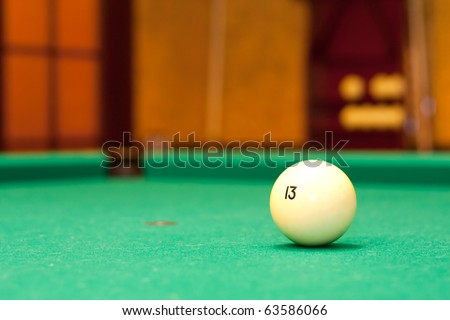 Billiard ball on green table against pocket