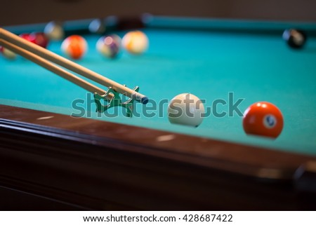 Billiard balls and cue on green table