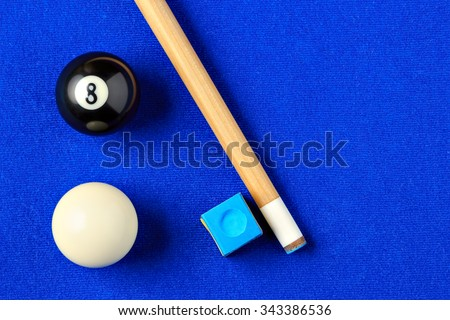 Billiard balls, cue and chalk on a blue pool table. Viewed from above. Horizontal image.