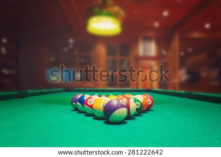 Billiard balls on green pool table in bar or pub - stock photo