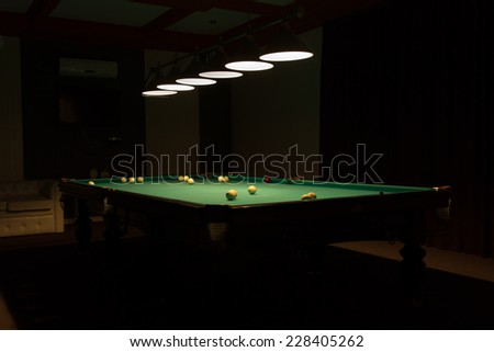 Billiard Balls Scattered on Pool Table in Empty Dimly Lit Pool Hall - stock photo