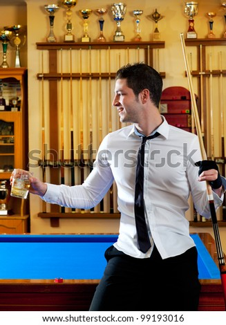 Billiard handsome young winner man with shirt tie and cue at trophy club - stock photo